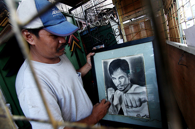 Artist Lando Jumalon, 42, shows the charcoal portrait of boxing icon and Sarangani Rep. Manny Pacquiao in his stall along San Pedro St. Davao City. Jumalon says he drew the portrait of the boxing star some years ago as a sample to his clients. Mindanews Photo by Keith Bacongco