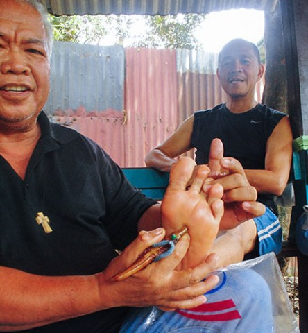 "The author with Kokoy and his ""handgun,"" a deer's horn the latter uses for his reflexology. Photo courtesy of Joma Bungabung"