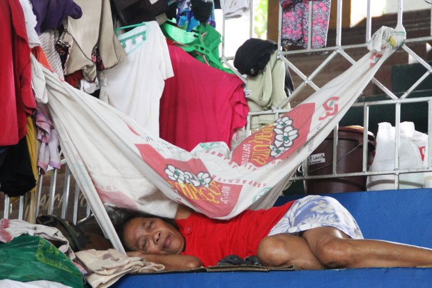 A woman who is among the residents who were displaced by the flood that hit areas along Panlibatuhan Creek in Valencia City on August 4, 2015 takes a nap inside the city gymnasium on August 6, 2015. MindaNews photo by H. Marcos C. Mordeno