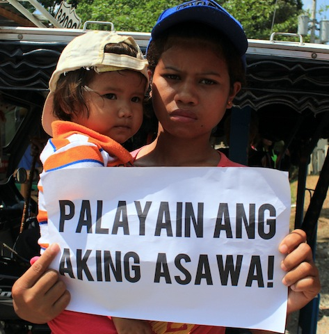 Wife and child of Henry Delgado, Jr. join a picket outside the Hall of Justice Compound in Kidapawan City on Wednesday morning where the motion to reduce bail for the 77 detained farmers was granted. MindaNews photo by GG BUENO