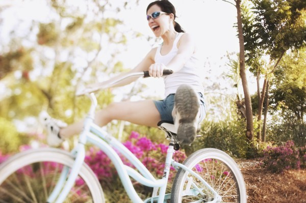 Woman on Bicycle with Legs Outstretched