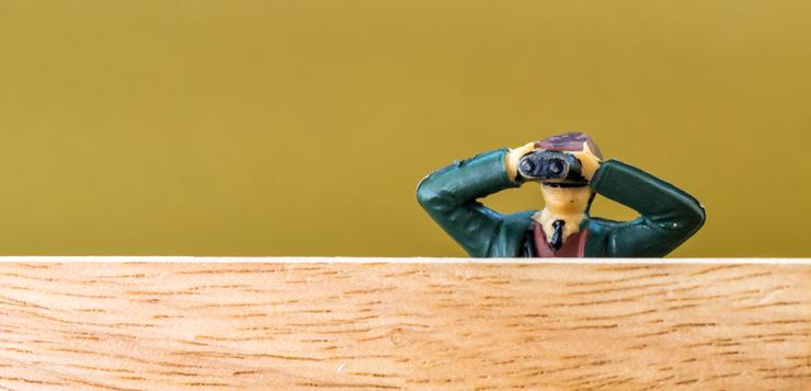 miniature man looking through binoculars