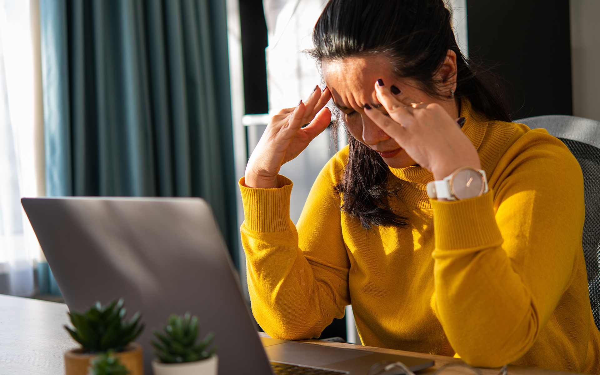 3 Ways Leaders Can Prevent Emotional Drain - Woman sits at her desk stressed out with her head in her hands