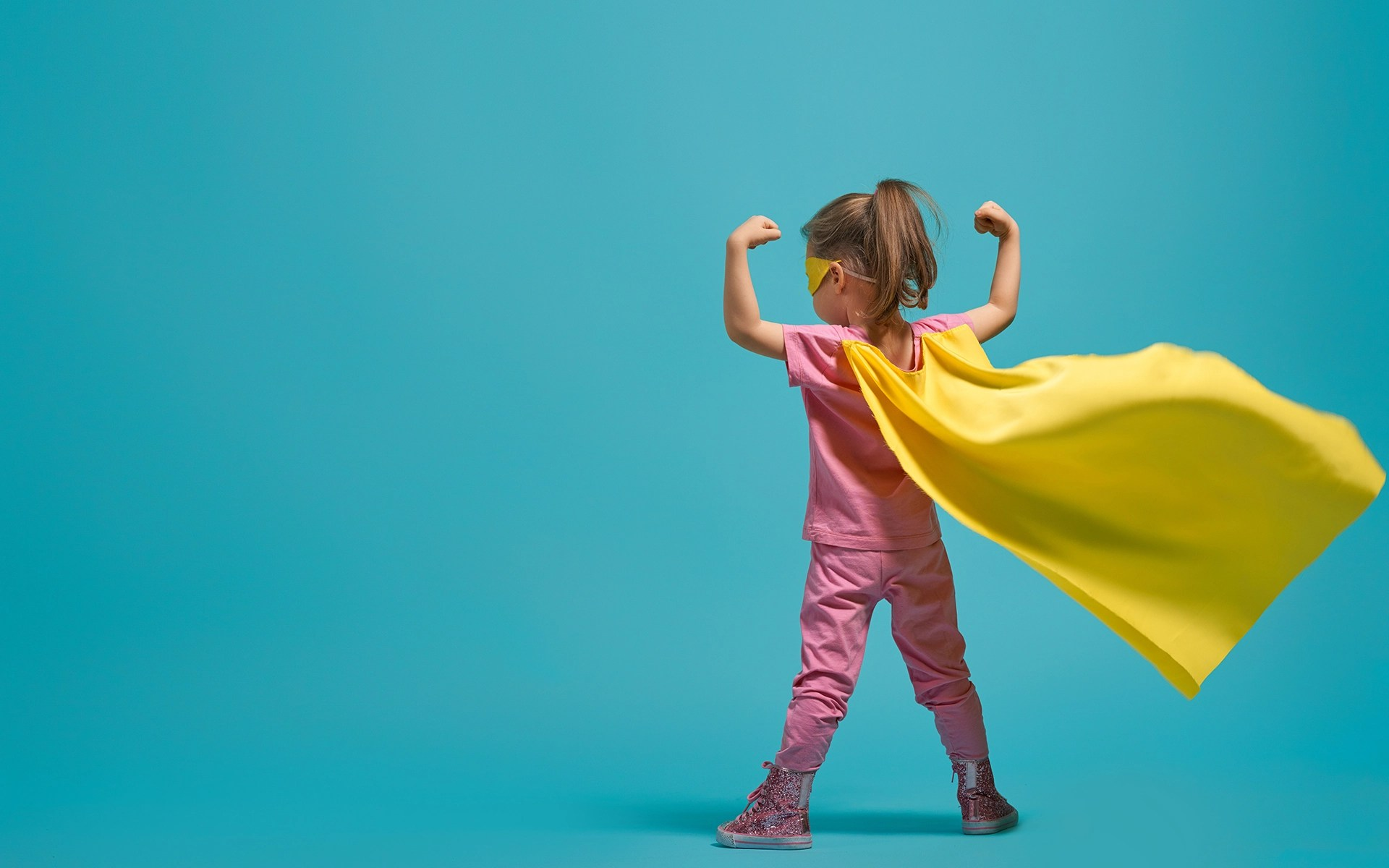 3 Mindful Practices for Resilient, Happy Kids - Little child playing superhero. Kid on the background of bright blue wall. Girl power concept. Yellow, pink and turquoise colors.