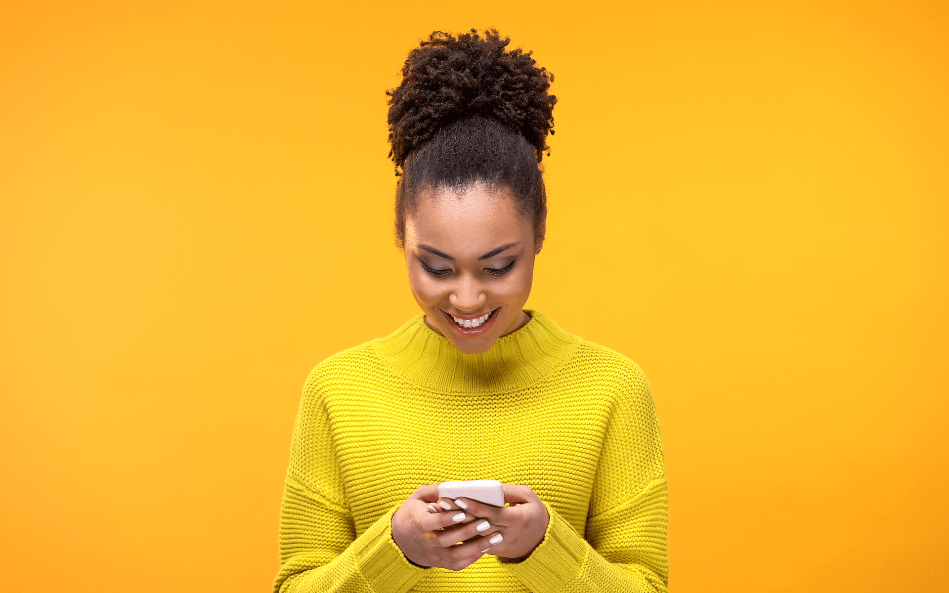 Black woman in a yellow T-shirt smiling down at her phone with a yellow studio background.