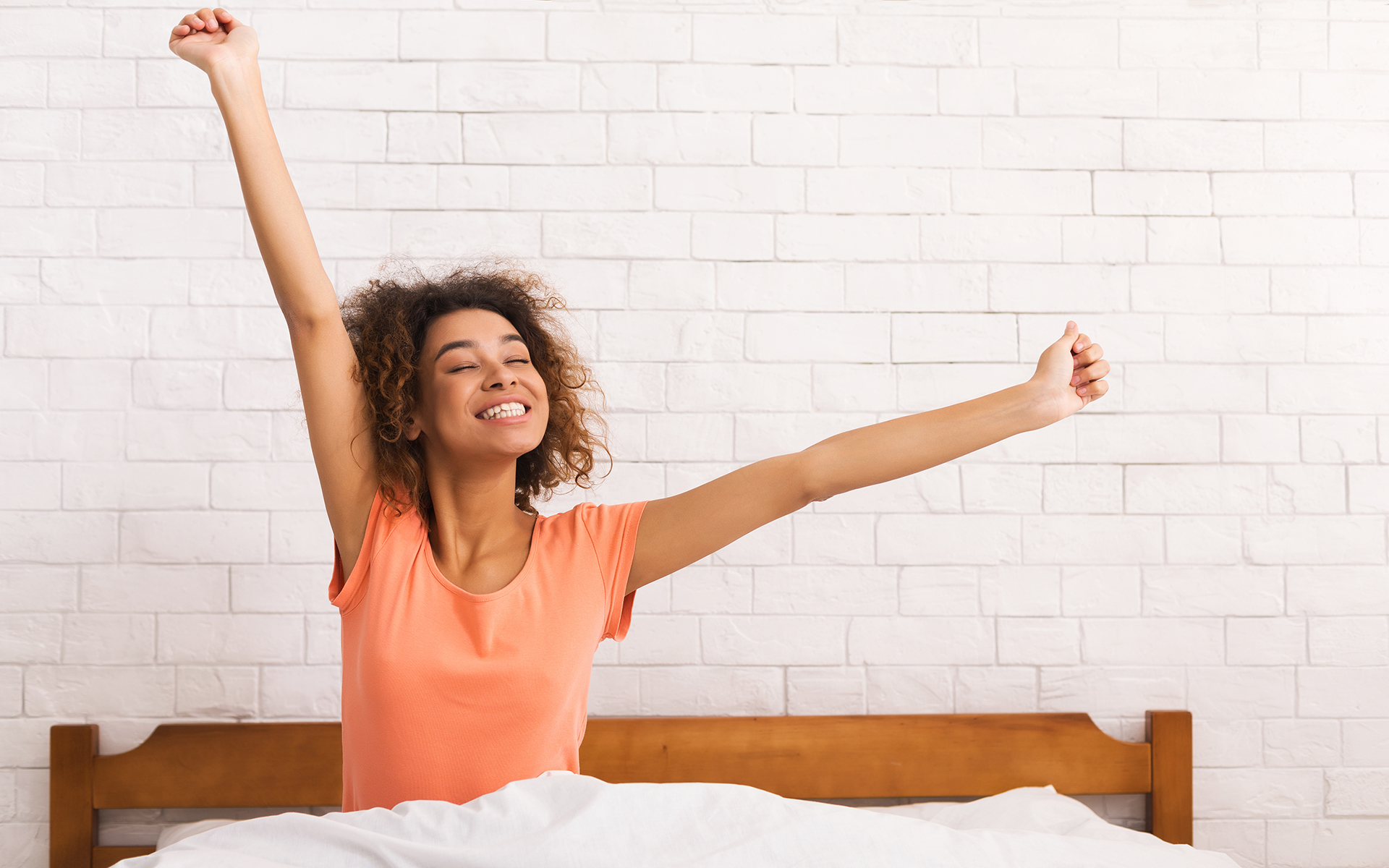 8 Science-Backed Tips for Better Sleep - Lazy morning. African-american woman stretching, sitting on bed