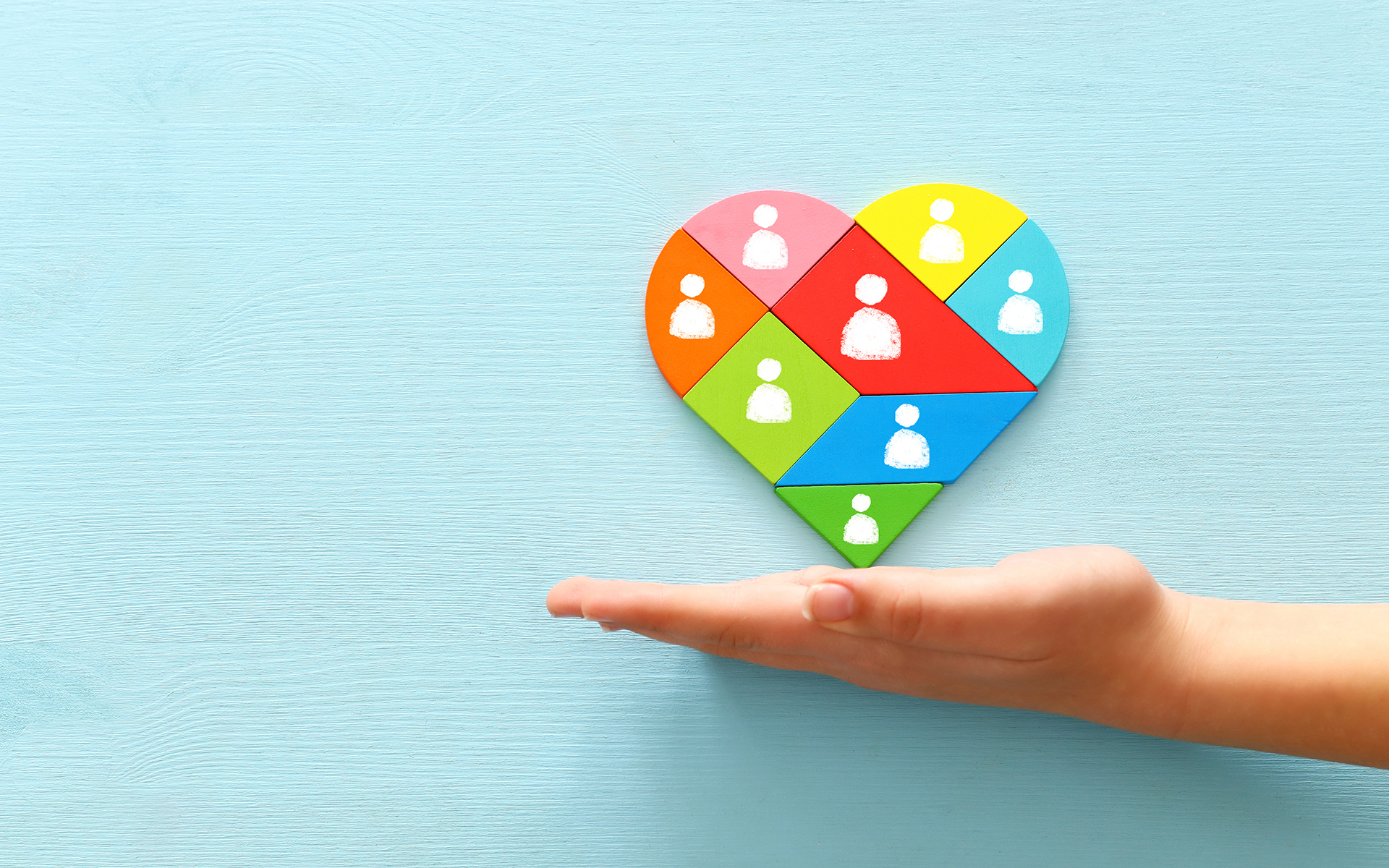 A Q&A with Miki Kashtan - image of heart shape tangram puzzle blocks with people icons over wooden table ,human resources and management concept