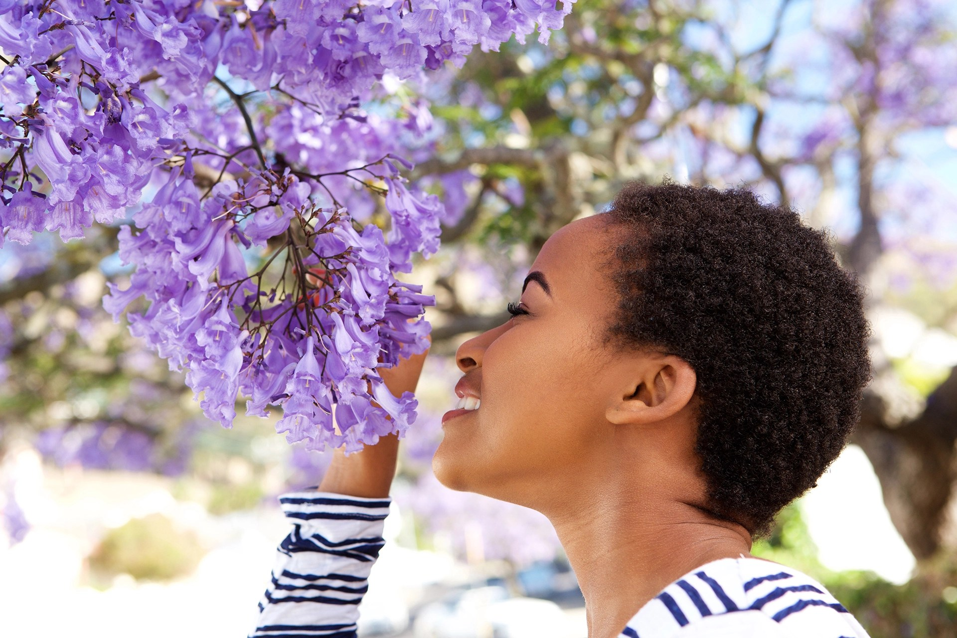 A guided meditation to invite nature into your life - Portrait of young black woman smelling flowers on tree