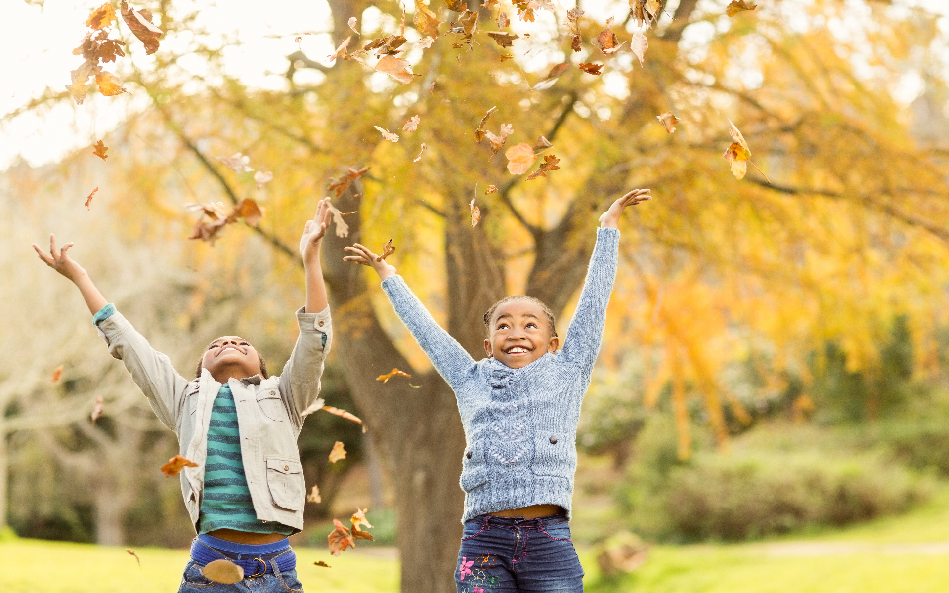 Two young girls playing in autumn leaves and smiling