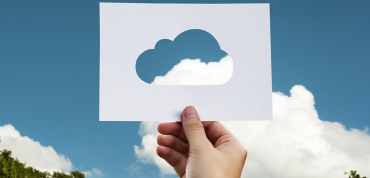 woman holding cloud stencil up to sky