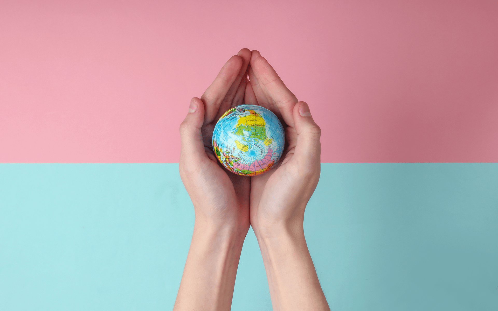 Do You Know How You Can Change the World?—We look down on someone's hands that are cupped together holding a small globe. The top half of the background is pink and the bottom half is light blue.