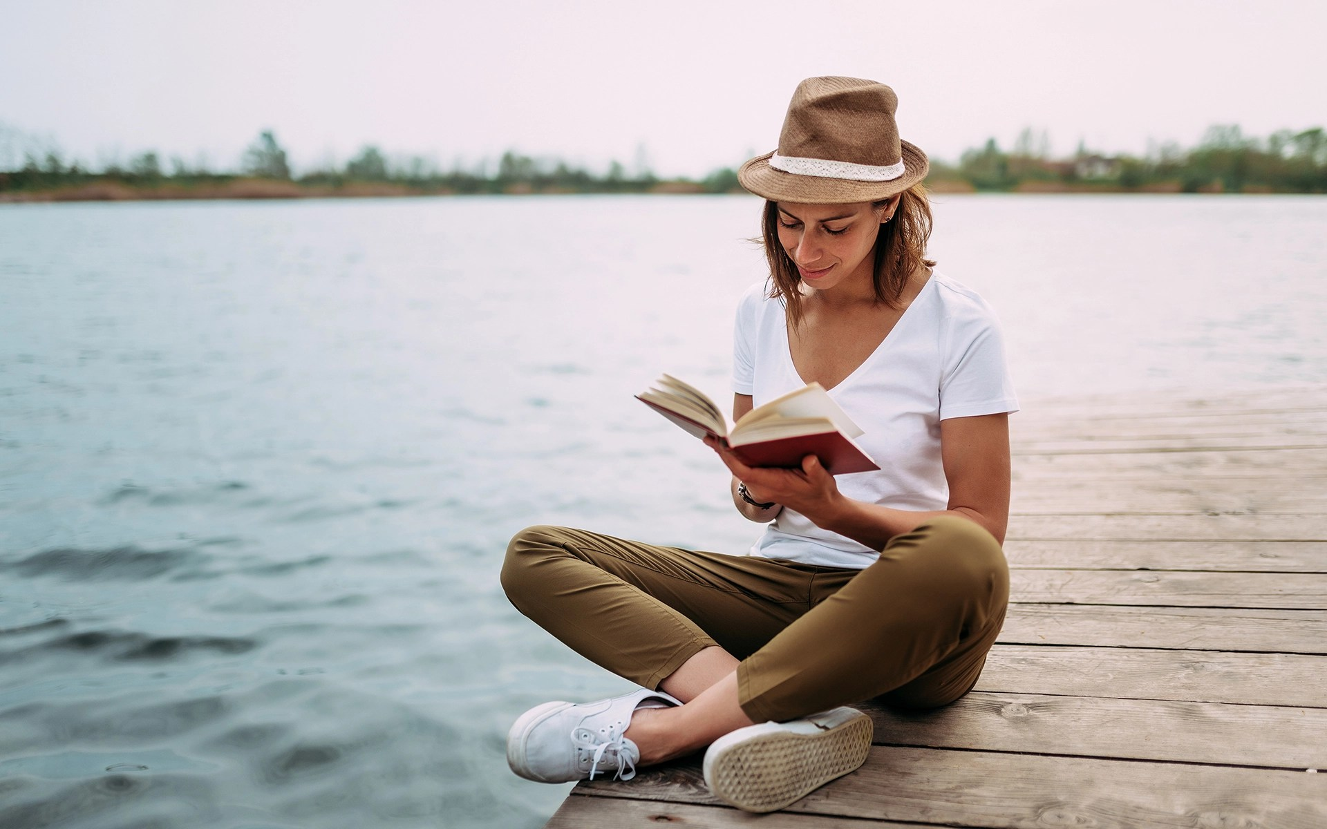 Five Mindful Books to Read Right Now - Portrait of a girl reading a book while sitting on a small wooden wharf.