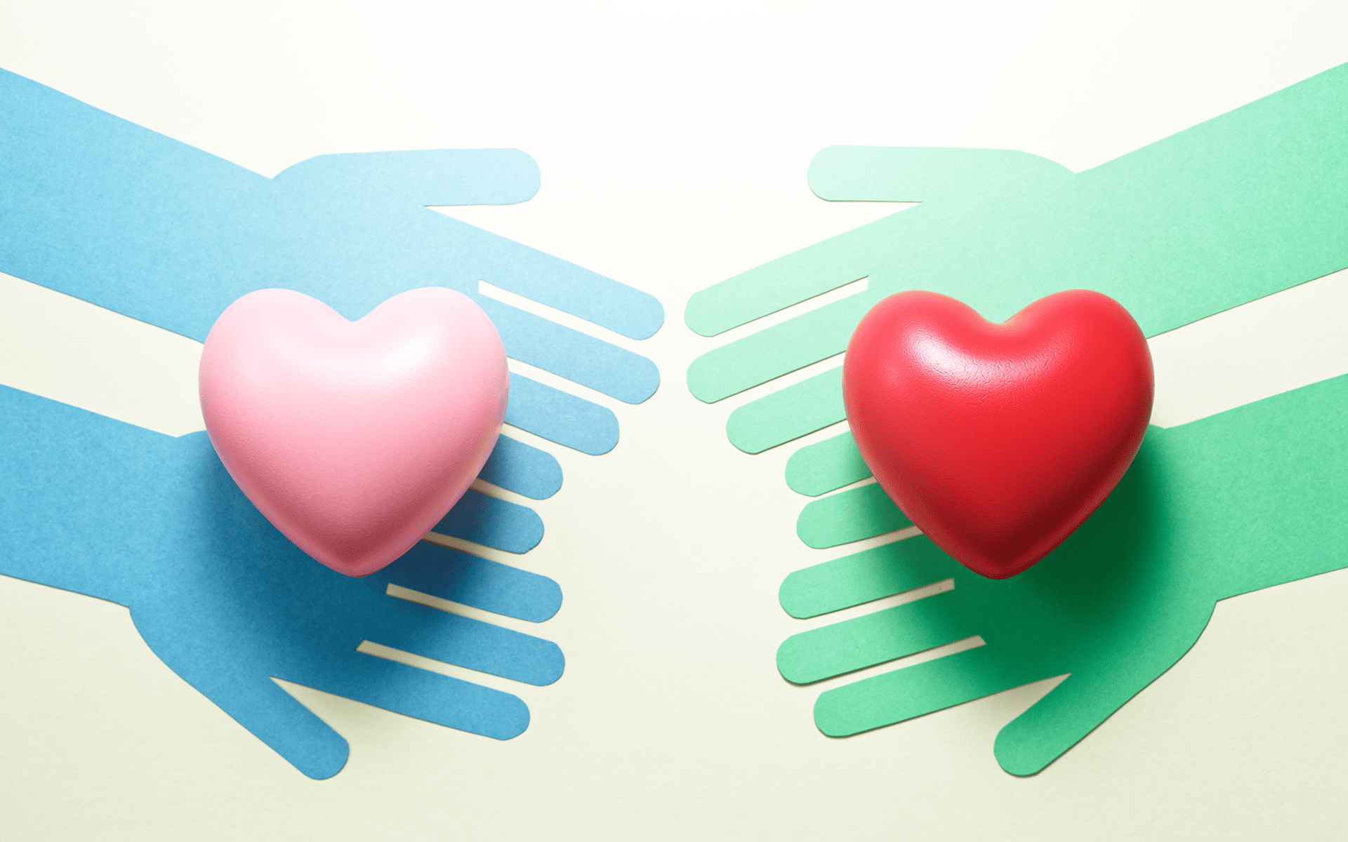 Paper cut outs of two blue hands and two green hands each reaching toward each other with a heart on each set of hands.