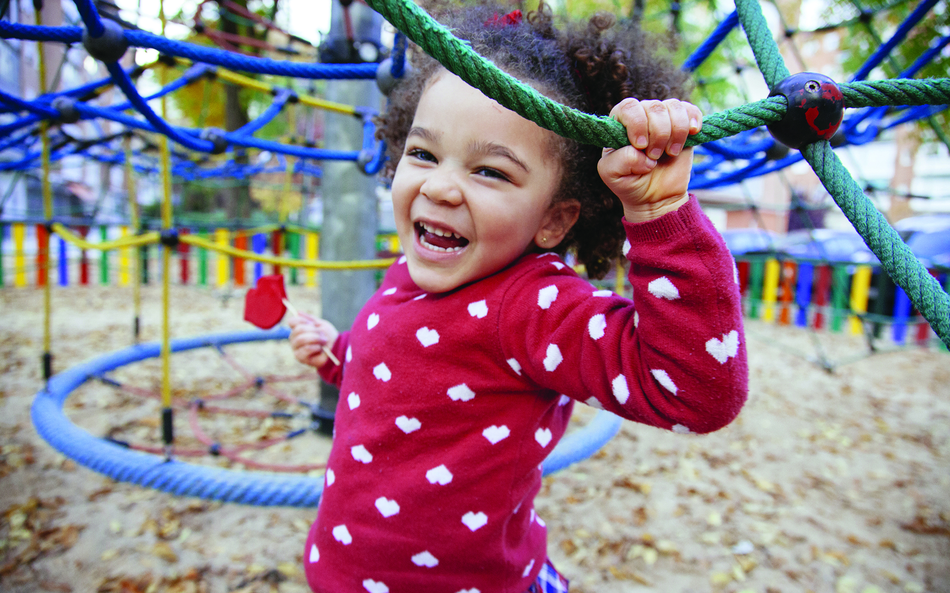 Smiling child wearing red sweater with white polka dots playing on jungle gym in outdoor playground.