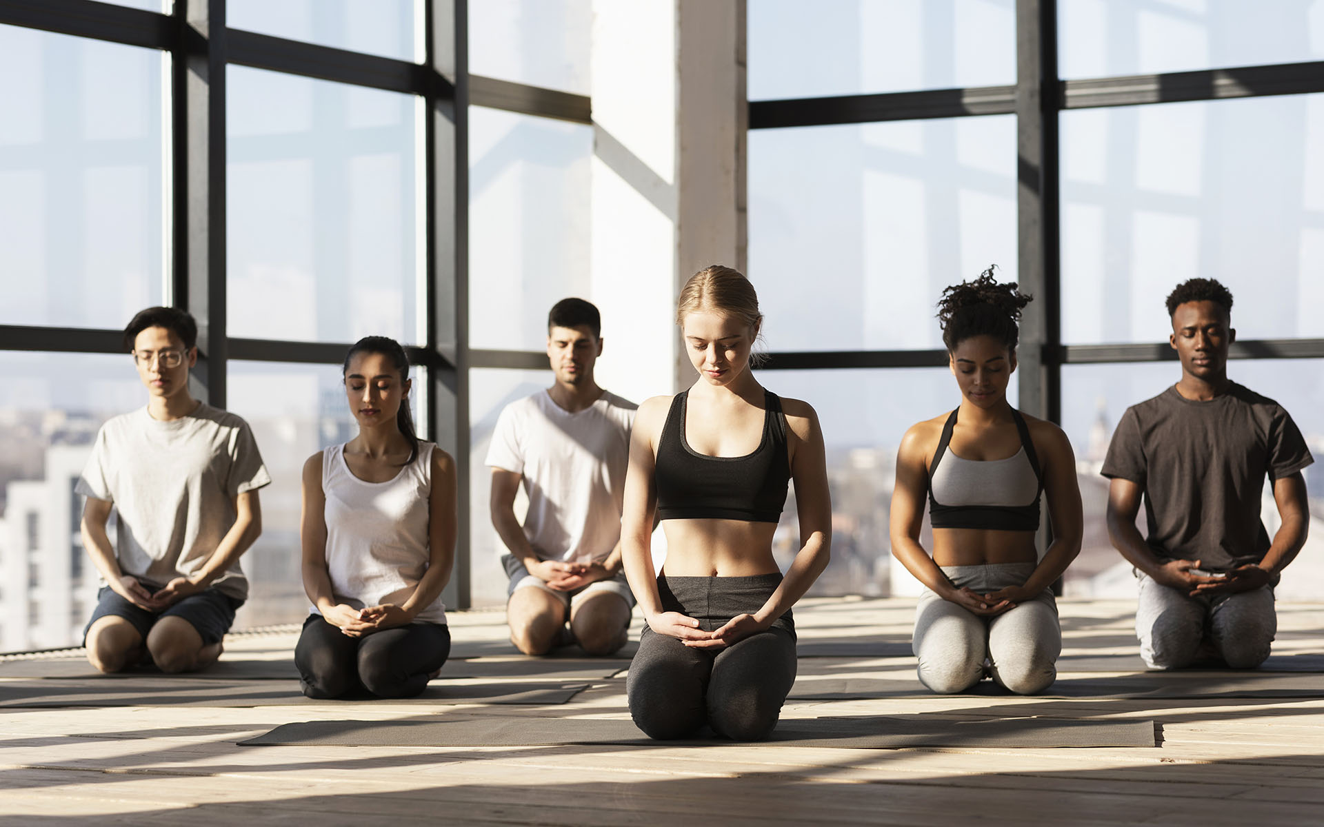 Your Friendly Neighborhood Meditation Studio - Young women and men making meditation exercises during yoga class
