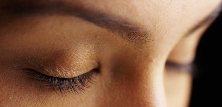 women eyes closed on black background