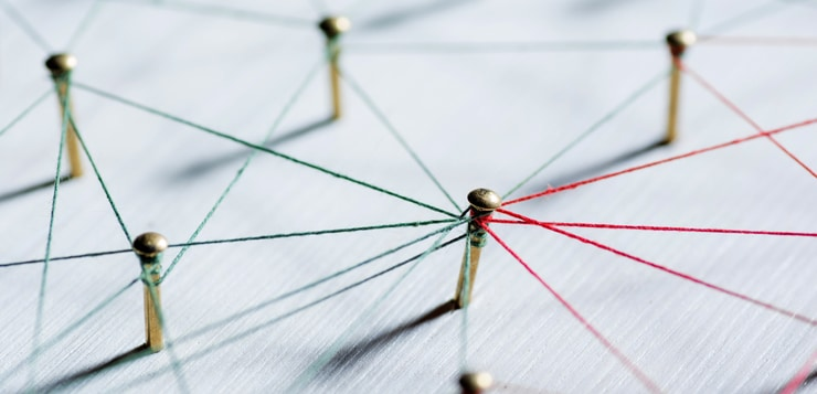 Thumbtacks linked together by red thread