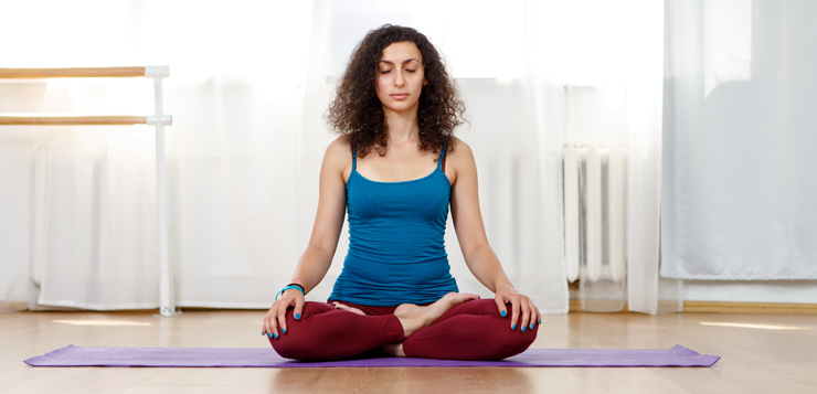 woman in seated meditation in living room