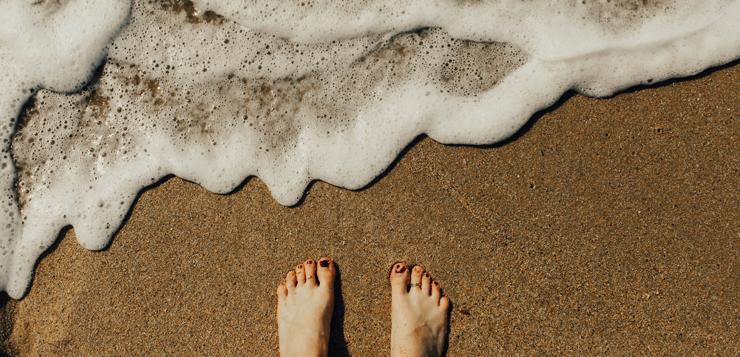 woman on beach, waves washing over feet