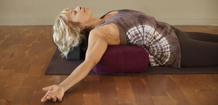 woman on yoga mat with bolster