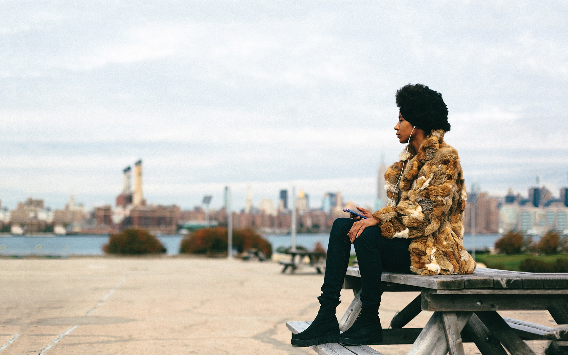 woman in vintage fur coat sitting on bench