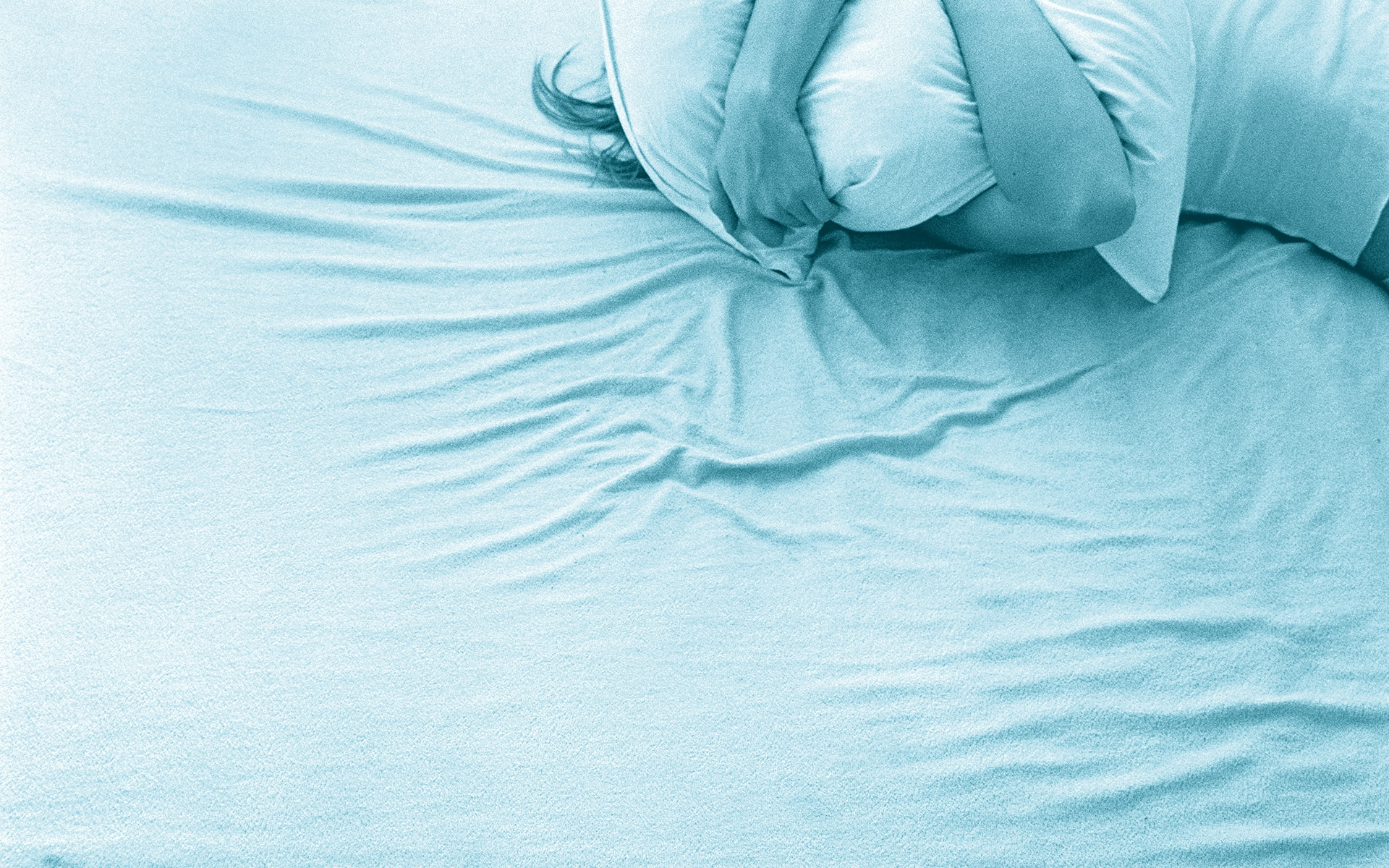 woman in bed holding pillow over face, not wanting to be seen