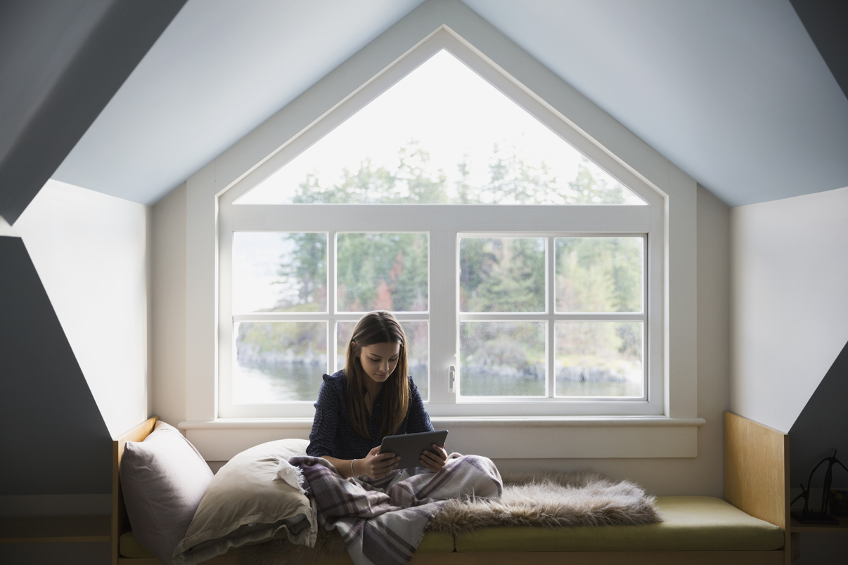 woman sitting and reading a book in her attic