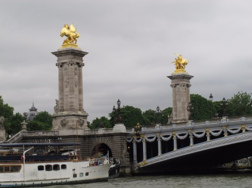 Paris: Two of the Four gilt-bronze statues of Fames watching over the bridge. Supported on massive 17 metres (56 ft) masonry socles, that provide stabilizing counterweight for the arch, without interfering with monumental views. The socles are crowned by Fames restraining Pegasus. Pont Alexandre III.