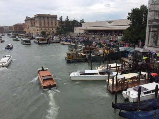 Venice Station: Venice Santa Lucia Station. Down the steps. Walk. Waterbus. Launch. Gondola. A man with a barrow.