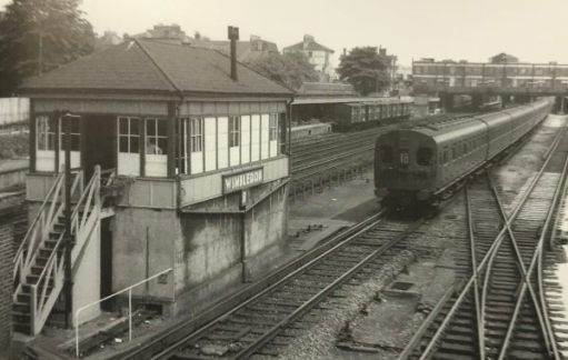 """The Footbridge: 1957 again. A modern, for its day, 4-SUB electric train. The freight vans in the background once again at the """"Milk Dock""""."""