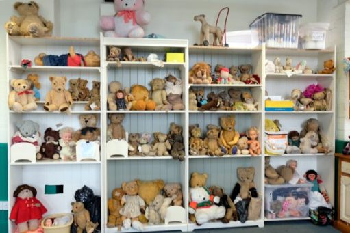 Bertie amongst a load of other bears on shelves at Alice's Teddy Bear Hospital.