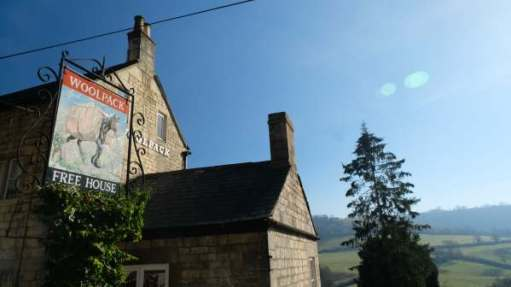 Cotswold Reverie: The Woolpack. Immortalised by Laurie Lee. Swift's Hill behind the pine tree.