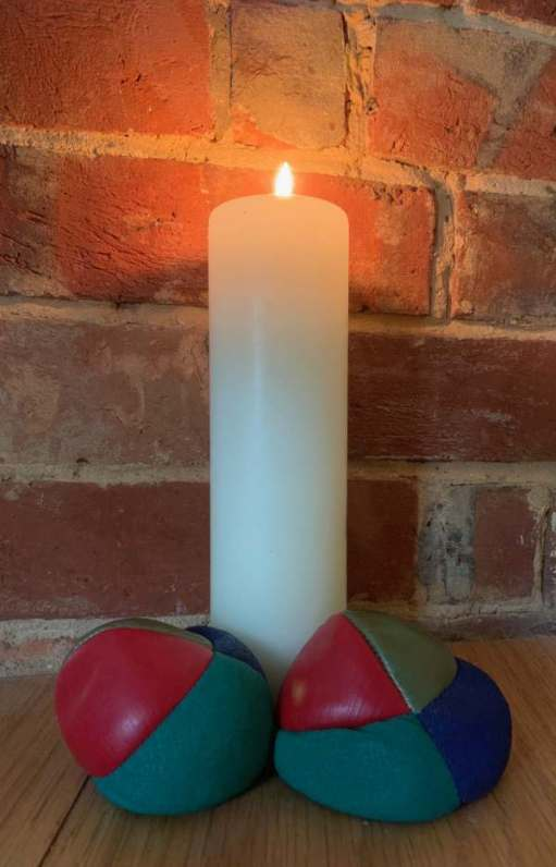 More Balls Than Most: Lighting a Candle to Diddley - Picture of a lit candle and two of the juggling balls.