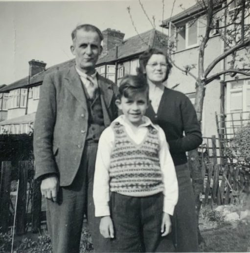 An older Bobby stood in front of his parents in the back garden of their house. A sense of belonging?
