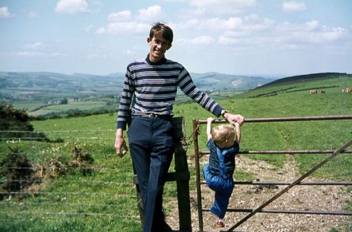 Bobby posing by a gate facing the camera, whilst his son is climbing up on the gate. The rolling hills of the Purbeck peninsula are in the background.