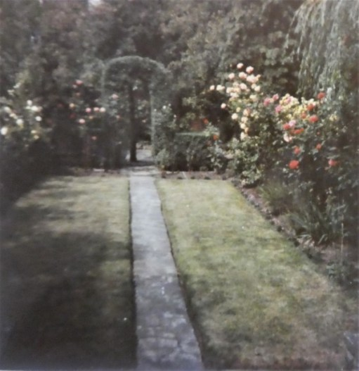 Colour shot of the garden. Laid mainly to lawn, a path runs down the middle. High flowers, as a hedge, run down both sides. A low hedge, trimmed into a archway over the path, goes across the far end.