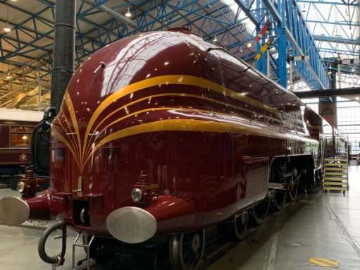 """Duchess of Hamilton. A beautiful maroon streamlined steam engine, with yellow/gold """"cats' whiskers"""" painted for effect. The front is rounded."""