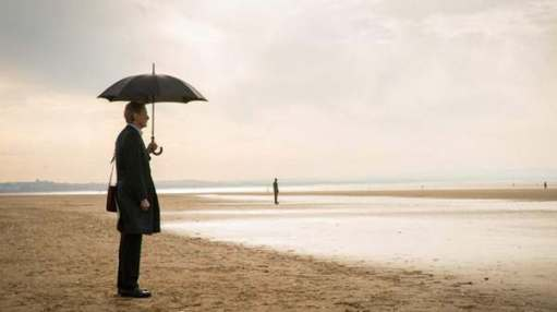 Picture of a beach on a grey day. Several loan people standing dotted around in the distance. In the foreground, a man in a coat, satchel over his left shoulder, holding an umbrella in his left hand.