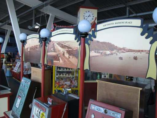 Historic images of coastal resorts above old slot machines on Southport Pier.