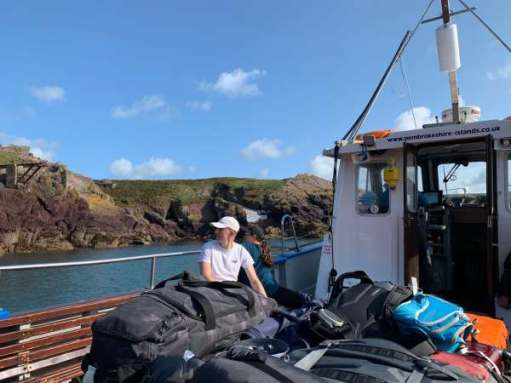 On the ferry. Two people, both called Sam, are viewed behind a big pile of luggage as they look back at the island.