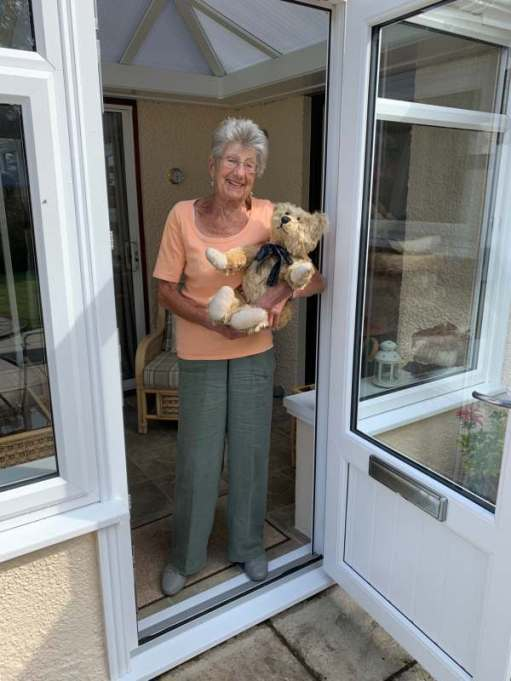 Bertie in Rosemary's arms in the doorway of her conservatory.