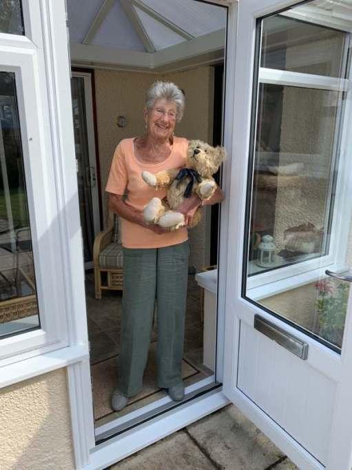 Bertie in Rosemary's arms in the doorway of her conservatory.