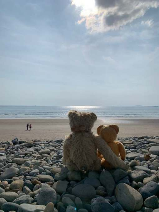 Bertie sat on a pebble beach with his right arm around Eamonn looking out to sea.