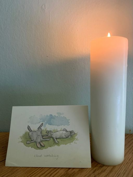 A candle lit for Diddley alongside a beautiful art water colour card of two hares lying on their backs cloudwatching.