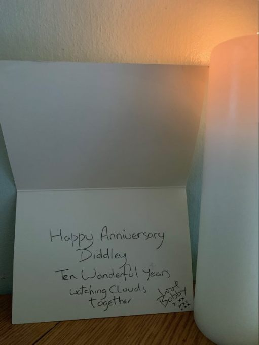 """The inside of the card, handwritten with: """"Happy Anniversary, Diddley. Ten wonderful years watching clouds together. Love Bobby"""" with 9""""x""""'s in three rows."""