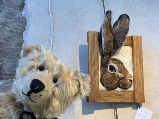 Bertie is posing in front of a 3D picture of a rabbit's head. The ears are sticking up over the top of the frame.