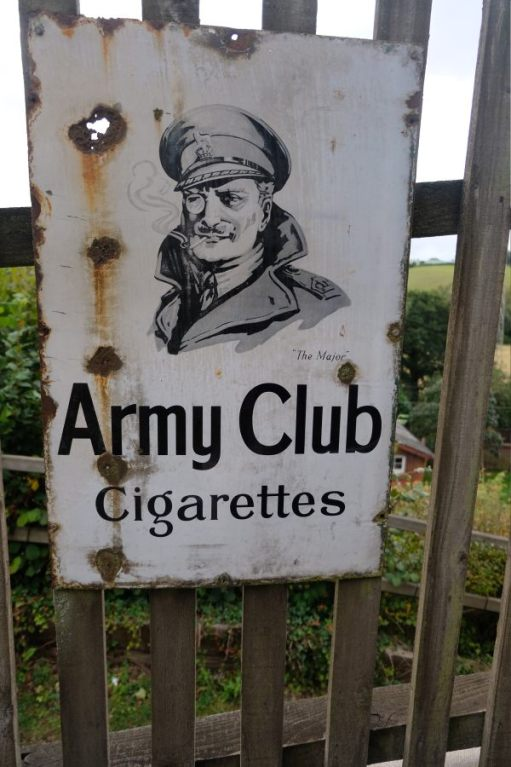 "West Somerset Railway - Enamel Sign ""Army Club Cigarettes"" attached to a station fence."