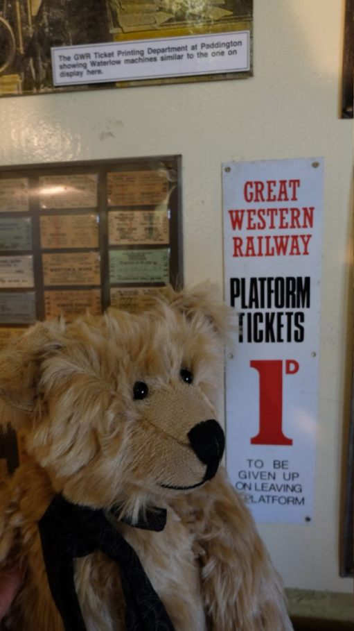 Somerset & Dorset Railway Trust: Bertie standing in front of an old Great Western Railway enamel sign advertising Platform Tickets at 1d - to be 'given up on leaving the platform'!