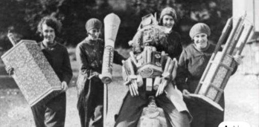 Four female workers at the Brocks Fireworks Factory holding some very large fireworks and a guy - presumably for a display.
