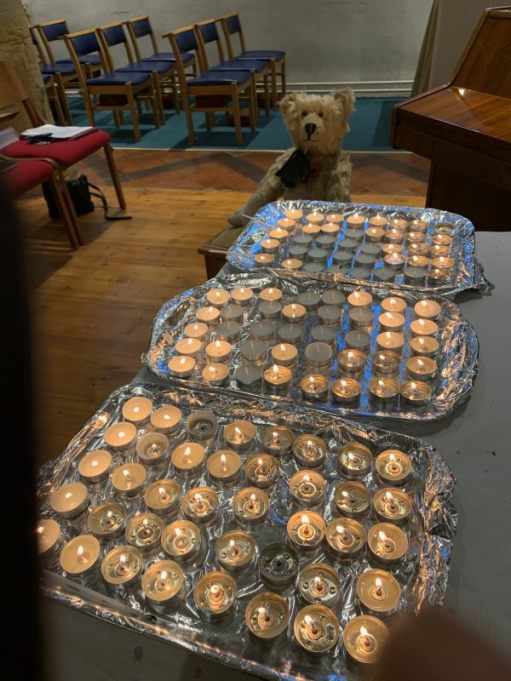 Bertie by three trays of lit candles to remember those who are not with us any more. We have lit a candle for Diddley.